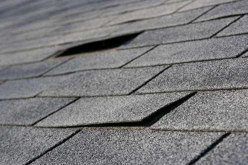 Damaged roof shingles in need of replacement